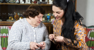 caregiver helping an old woman to knit a yarn