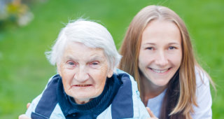 smiling old woman together with her caregiver
