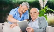 caregiver assisting an old man using a tablet